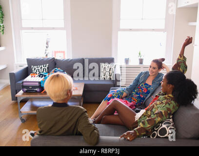 Young women friends hanging out in living room - Stock Image