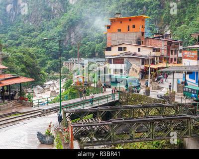 Aguascalientes, Peru - January 5, 2017. View of the tourists walking in  Aguascalientes village in a rainy day - Stock Image