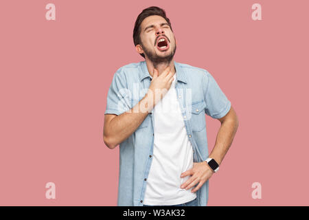 Throat pain or cold flu. Portrait of sad sick handsome bearded young man in blue casual style shirt standing and holding his painful neck and screamin - Stock Image