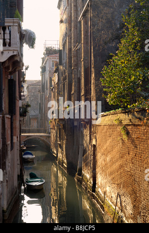 An empty Venetian backwater canal with reflections of late afternoon winter sun. - Stock Image
