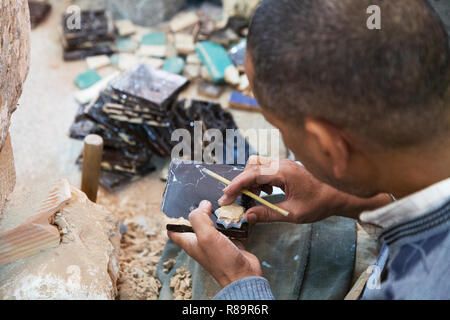 Marrakech craftsman - a man hand painting tiles, Marrakech medina, Marrakech Morocco North Africa - Stock Image