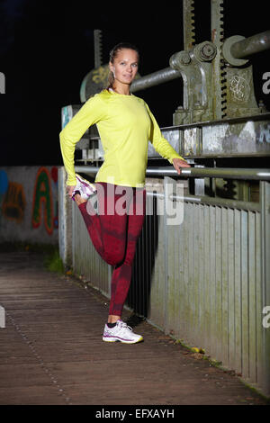 Young woman warming up on footbridge at night - Stock Image
