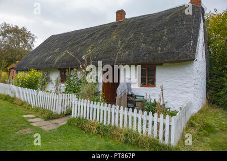 White Cottage late 18th century Cruck building with woman in period dress in garden  at Ryedale Folk Museum in Hutton le Hole North Yorkshire England - Stock Image