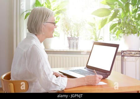 Senior woman at home in front of her laptop taking notes, online advice or e-learning concept template, blank screen, - Stock Image