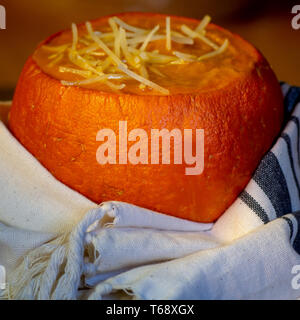 Pumpkin soup in baked mini-pumpkin wrapped in white dish cloth against brown- seasonal dish - Stock Image