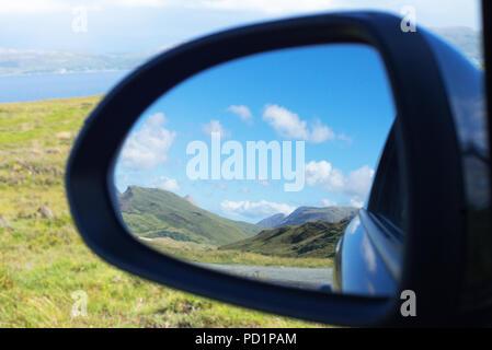 Cuillin Mountain range seen through the rear view mirror of a car in Isle of Skye, Scotland - Stock Image