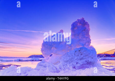Backlit ice glowing in the sunset on the St Lawrence river at Cap Rouge near Quebec City, Canada - Stock Image