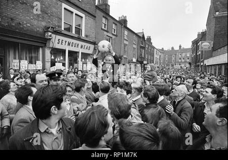 The traditional Royal Shrovetide Football Match, a 'medieval football' game played annually on Shrove Tuesday and Ash Wednesday in the town of Ashbourne in Derbyshire. Guest of honour Sir Stanley Matthews is carried shoulder high  by villagers through the main street toward the start point of the game. 22nd February 1966. - Stock Image