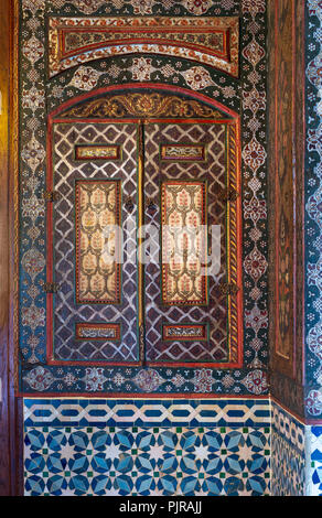 Embedded vintage cupboard painted with colorful floral patterns at Syrian hall of historic Manial palace of Prince Mohammed Ali, Cairo, Egypt - Stock Image