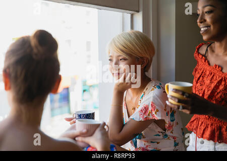 Young women friends drinking coffee at apartment window - Stock Image