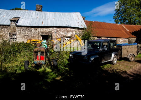 Collpses farmhouse and barn with decaying machinery on working upland farm Herefordshire UK 2018 - Stock Image