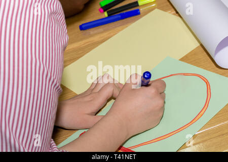Student hand with blue felt pen drawing on green paper on desk in classroom. Colorful pens spilled on paper. Education concept. Close up - Stock Image