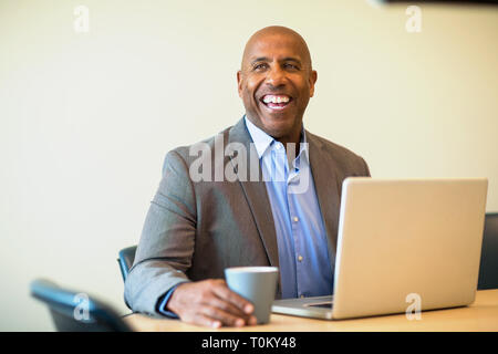 Mature African American man smiling at work. - Stock Image