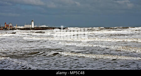 Choppy seas, created by strong inshore easterly winds, batter Scarborough's sea wall in South Bay. - Stock Image