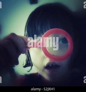Little Girl Looking Through A Toy Magnifying Glass - Stock Image