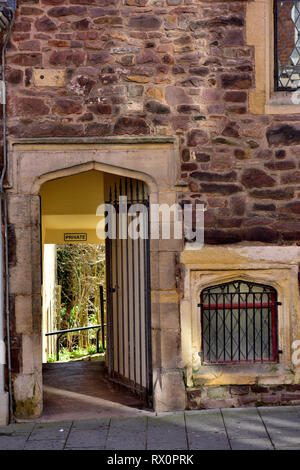 Old barred entrance way, barred window in stone wall - Stock Image