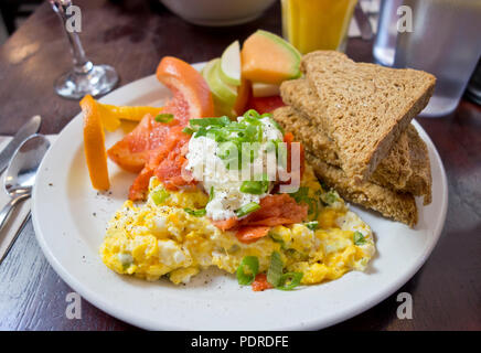 Delicious breakfast with scrambled eggs, smoked salmon,toast, and fruit. Served at Mole Cafe in Victoria, BC, Canada. - Stock Image