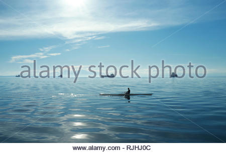 A canoeist off the waterfront in Thessaloniki, with large vessels in the distance anchored in the Aegean Sea. Thessaloniki, Central Macedonia, Greece. - Stock Image