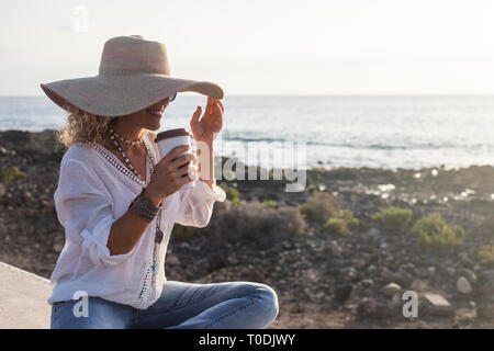 Holiday summer style with fashion pretty woman smiling and drinking a coffee neat the ocean in outdoor vacation leisure activity - happy people hippy  - Stock Image