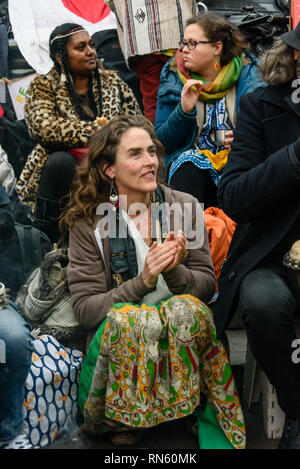 London, UK. 16 February 2019. Venus CuMara sits with the drummers. The 16th 'Reclaim Love' free Valentine's Day street party takes place around the statue of Eros in Piccadilly Circus, with drumming, music, dancing poetry to celebrate love. The event, which was founded by poet Venus CuMara, aims to reclaim love as a manifestation of the human spirit from the sleazy commercialisation which has taken over Valentine's Day as a festival of profit.  ake part Credit: Peter Marshall/Alamy Live News - Stock Image