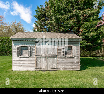 an old shed sitting in a green yard - Stock Image