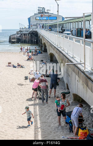 Bournemouth, UK. 11th June 2018. Tourists find some shade from the sun by the pier on Bournemouth beach and seafront. Credit: Thomas Faull/Alamy Live News - Stock Image