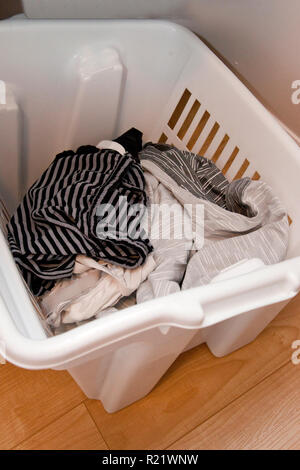 White laundry basket with clothes ready to be washed - Stock Image