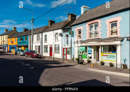 Colourful shops and houses on Main Street, Drimoleague, West Cork, Ireland on a sunny day. - Stock Image