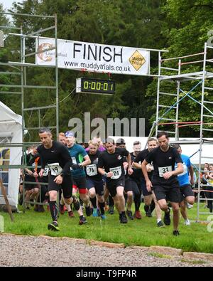 18th, May, 2019. Craufurdland Estate, Fenwick, Ayrshire, Scotland, UK. Participants have fun taking part in the 5k, 10k and the childrens 1 mile 'Muddy Trial fun run through woods and ditches full of water and mud in the Craufurdland Estate. - Stock Image