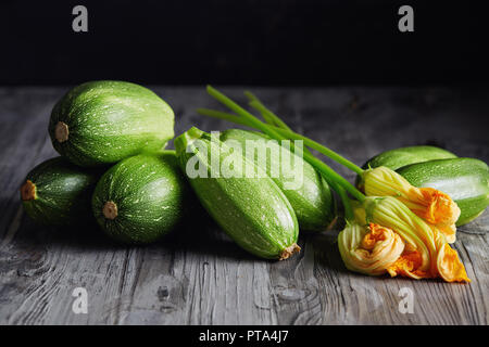 Zucchini and Zucchini Blossoms. Fresh green zucchini with flowers on rustic background. - Stock Image