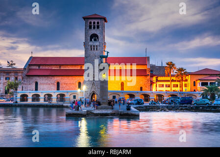 Rhodes, Greece. Stunning sunset image Mandraki harbour and Evaggelismos Church the place of Colossus of Rhodes. - Stock Image