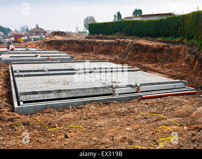 Modern shallow cinder block foundations on a new build construction site for building housing association affordable - Stock Image