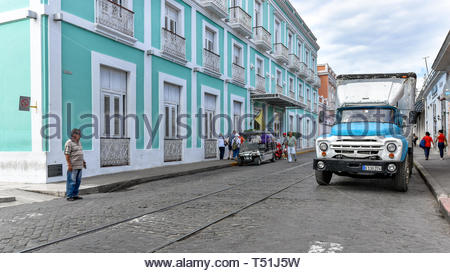Old obsolete Russian Zyl truck driving in D'Clouet street.  The 'Hotel Union' operated by Melia Hotels is to the left. There are unused train tracks i - Stock Image