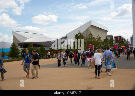 People walking and Water Polo Arena on a sunny day at Olympic Park, London 2012 Olympic Games site, Stratford London - Stock Image
