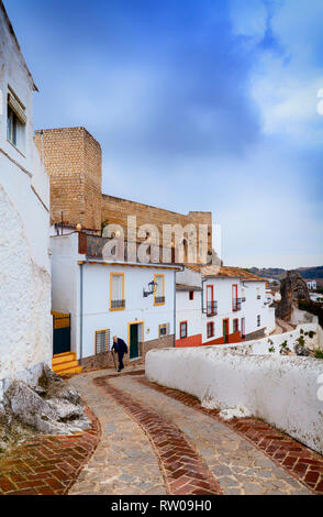 Old man below the 9th century, Berber Cañete la Real Castle towering above the town of Cañete la Real,  Province of Málaga, Andalusia, southern Spain. - Stock Image