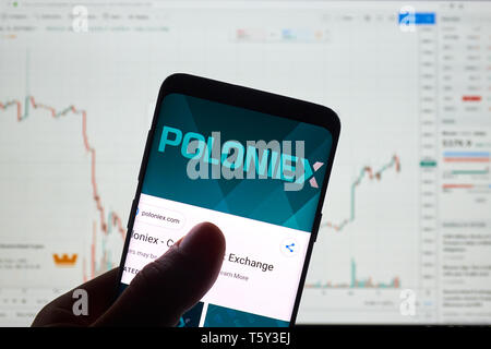 MONTREAL, CANADA - APRIL 26, 2019: Poloniex cryptocurrency exchange logo and application on Android Samsung Galaxy s9 Plus screen in a hand over a lap - Stock Image