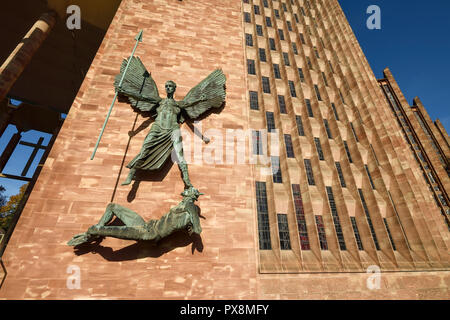 The statue of St Michael and the Devil outside Coventry Cathedral on Priory Street in Coventry city centre UK - Stock Image