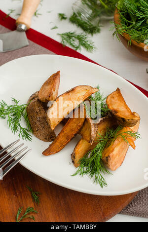 Baked potato wedges with dill. - Stock Image