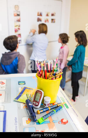Diabetic children participating in a therapeutic education workshop animated by a nurse. Pediatric department of Angouleme hospital, France. - Stock Image
