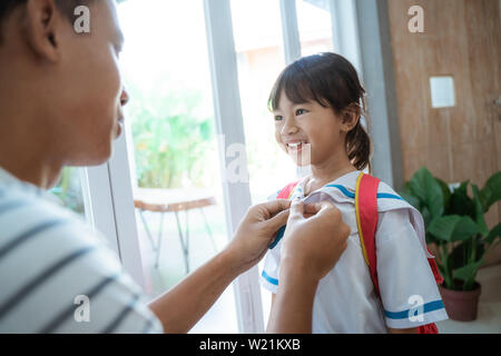 happy kid wearing school uniform her father help her to button the shirt on - Stock Image