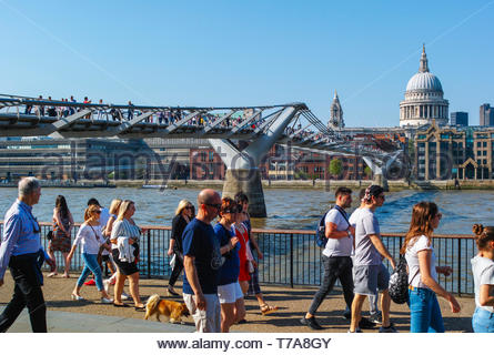 Crowds of people enjoying good weather in the city on the Millennium Bridge and between  St Pauls and Bankside: London. - Stock Image
