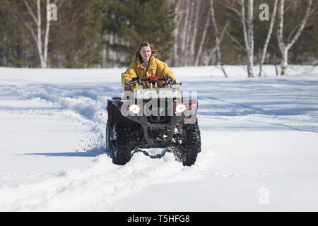 A winter forest. A young woman with long hair in bright yellow jacket riding snowmobile - Stock Image
