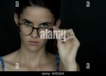 Young woman looking over the top of her glasses, portrait - Stock Image