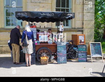 A man and a woman buying refreshments from a portable Coffee and cake stall on a coffee bike in Museum Park York - Stock Image
