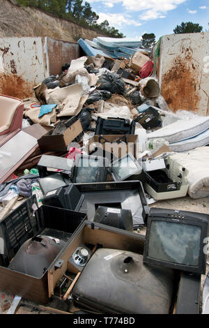 pile of old televisions & mattresses dumped in skip, Spain - Stock Image