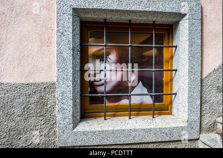 Fashion poster of a female in a barred window. - Stock Image
