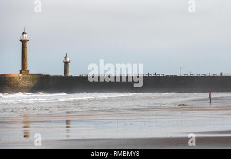 Woman standing on the beach at Whitby on the North Yorkshire coast with the old lighthouses in the background. - Stock Image