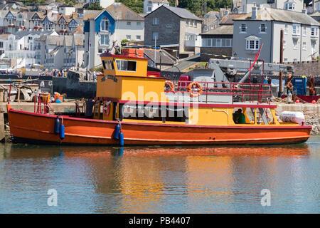 Tourist excursion boat Brixham Belle moored alongside the harbour wall at Brixham, Devon, UK - Stock Image