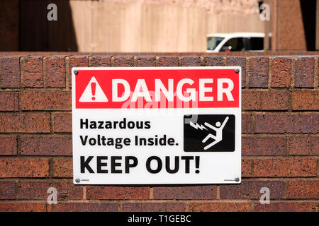 Danger sign or hazard sign, warning of hazardous high voltage power or electric lines and advising to keep out in Montgomery Alabama, USA. - Stock Image
