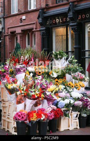 Bouquets of flowers for sale outside Boodies Jewellery Shop, Grafton Street, Dublin, Ireland. - Stock Image